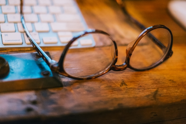 This photo shows a pair of glasses by a keyboard