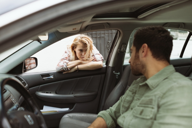 This photo shows a man in the driver seat talking to a woman leaning in through the passenger window