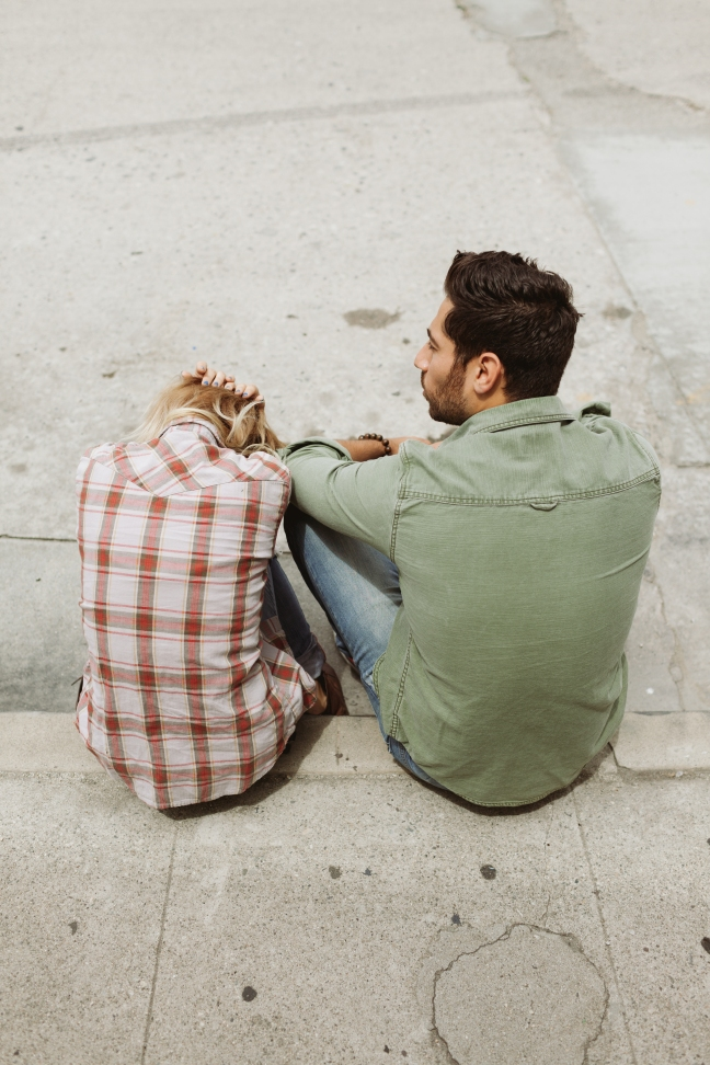 This photo shows the backs of a man and a woman sitting on a curb together.