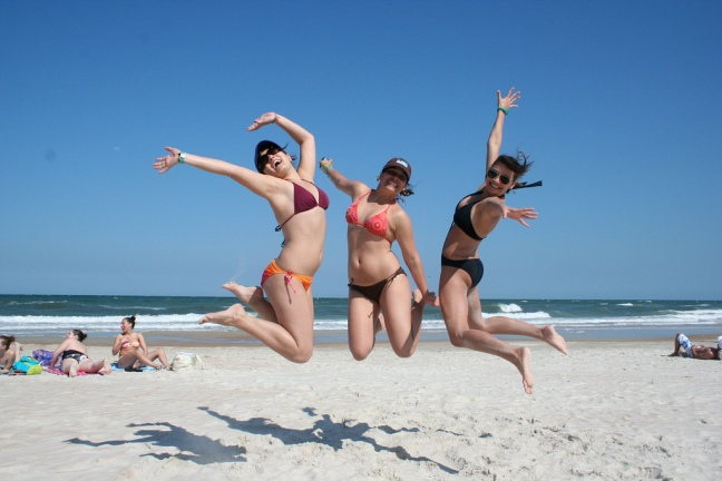 This photo shows three women jumping together on the beach