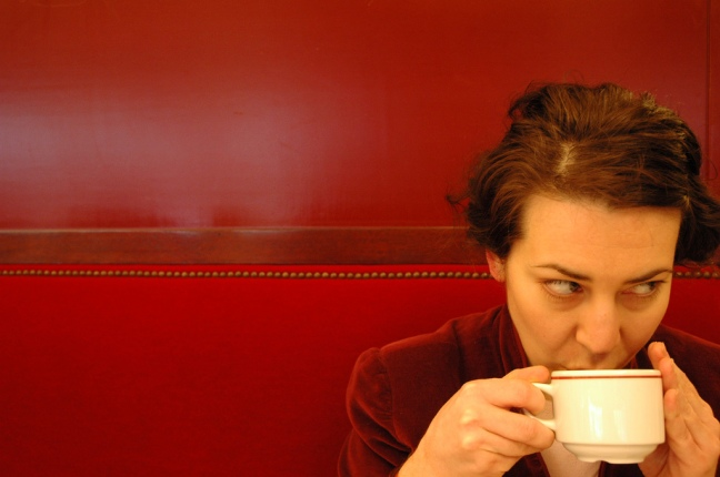 This photo shows a woman sipping coffee against a red wall and red booth