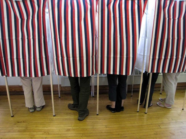 This photo shows voters' legs and feet behind red-white-and-blue striped voting booth curtains on election day