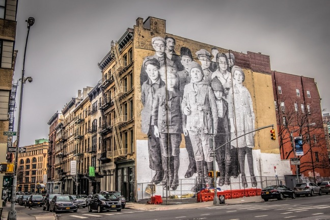 This photo shows a New York City billboard of Ellis Island children covering the side of a building