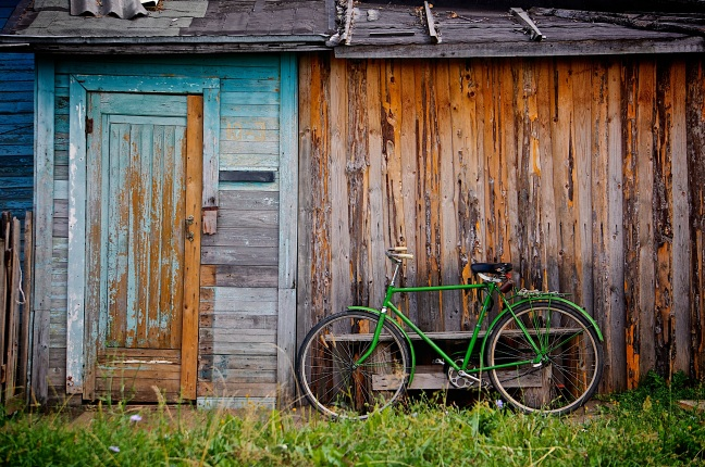 This photo shows a dilapidated barn with a green bicycle leaning against its front wall.