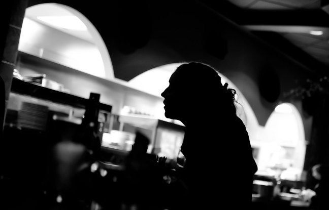 A waitress in a diner stands in profile silhouette in black and white